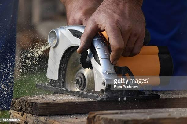 carpenter cutting wood with circular saw - gekarteld stockfoto's en -beelden