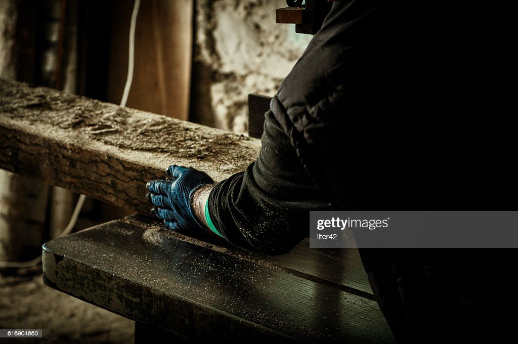 Carpenter cutting wood with saw : Stock Photo