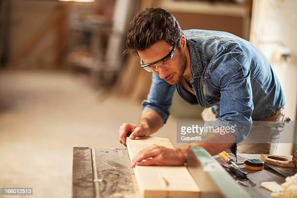 Carpenter cutting wooden plank