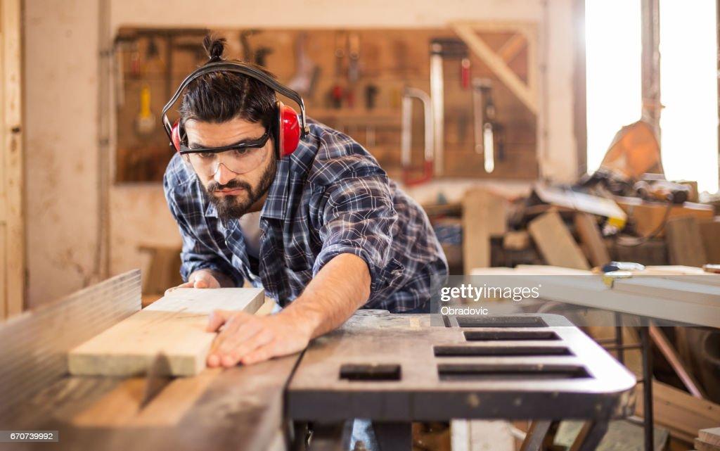 Carpenter cutting wooden plank : Stock Photo
