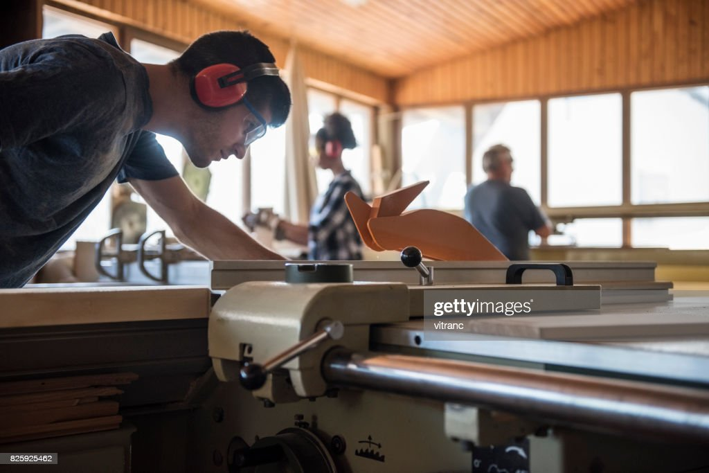 Carpenter cutting wooden plank : Stock Photo