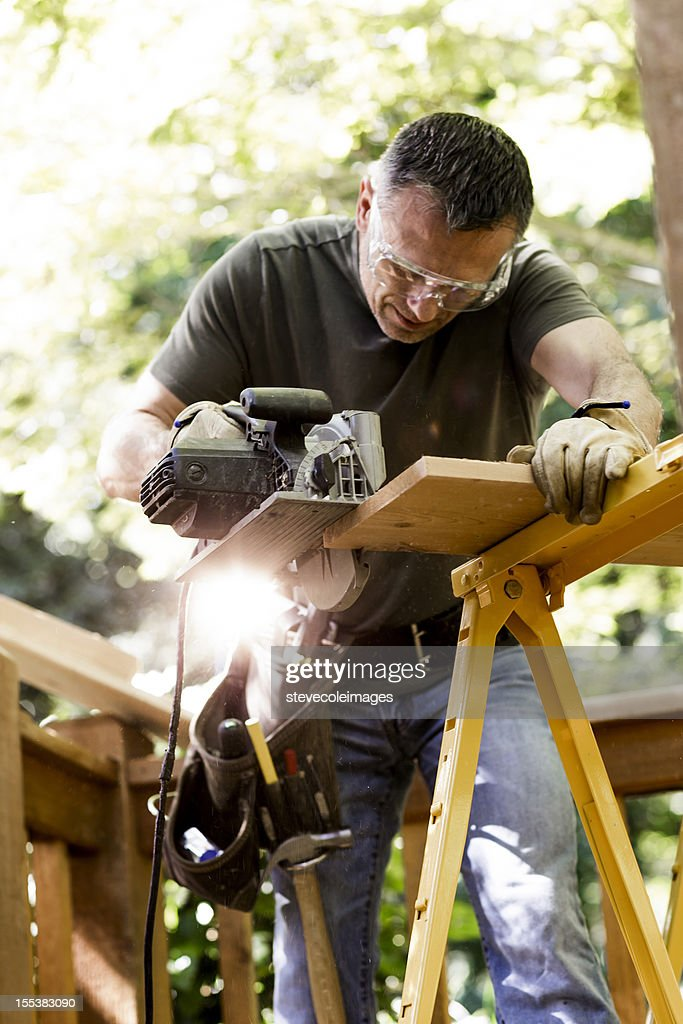 Carpenter Cutting Wooden Plank With Circular Saw. : Stock Photo