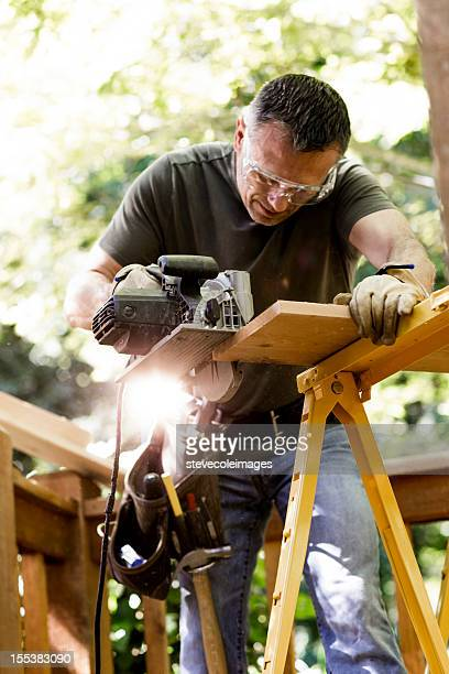 Carpenter Cutting Wooden Plank With Circular Saw.