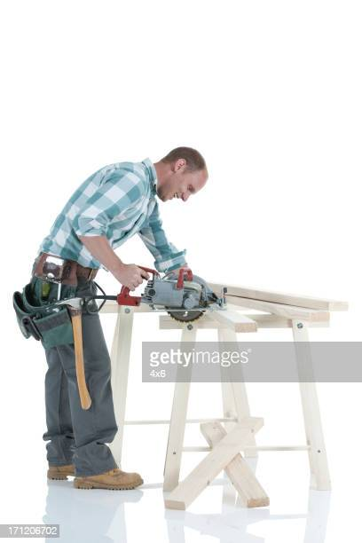 Carpenter cutting wooden planks