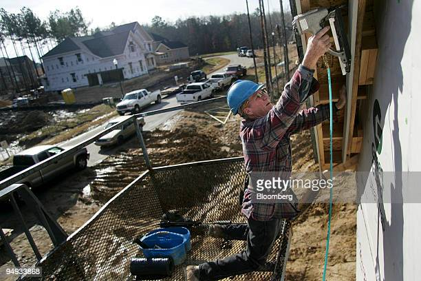 Carpenter Dennis Tyler installs face boards on a Toll Brothers Inc luxury home under construction in The Woodlands' Green Level Crossing in Cary...