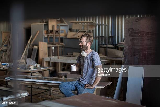 Carpenter drinking coffee in workshop