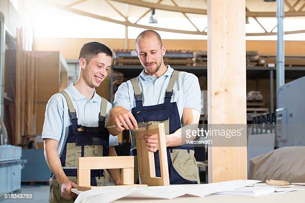 Carpenter examining work of a trainee
