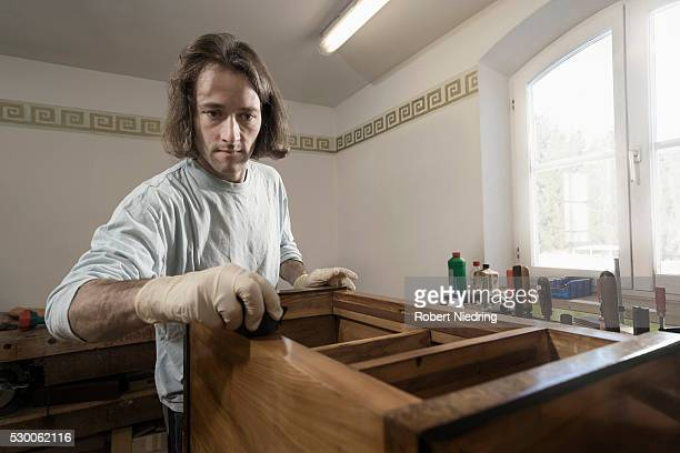 Carpenter French polishing on wooden drawer at workshop, Bavaria, Germany
