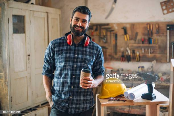 carpenter holding cup of coffee - damages compensation stock pictures, royalty-free photos & images