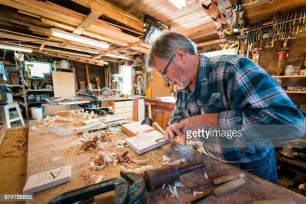 Menuisier dans son atelier de sculpture sur bois avec le ciseau