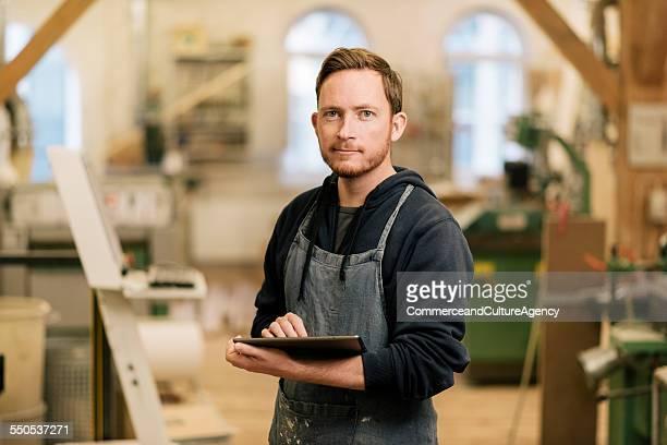 carpenter in wood workshop using tablet