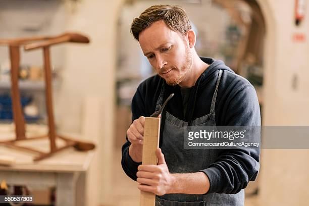 carpenter in wood workshop working on chair