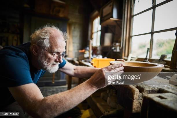 carpenter in workshop working on a wooden bowl - handgemacht stock-fotos und bilder