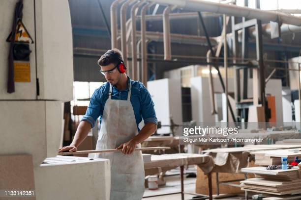 carpenter inserting wood in machine at factory - inserting stock pictures, royalty-free photos & images