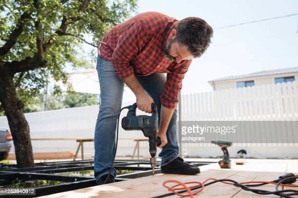 carpenter installing a wood floor outdoor terrace in new house construction site - deck stock pictures, royalty-free photos & images