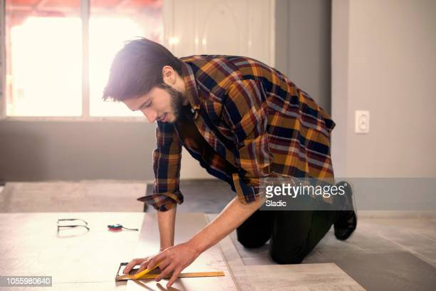 carpenter installing a wooden flooring - laminate flooring stock pictures, royalty-free photos & images