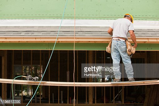 Carpenter Installing Flashing Above Garage Door Stock