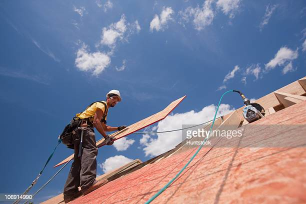 Carpenter installing 'L' shape panel on the roof of a house under construction
