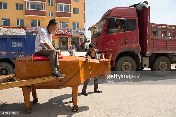 Carpenter Li Jingyang rides his homemade wooden ox replica on July 8 2015 in Yongji County Jilin City Jilin Province of China 61yearold carpenter Li...