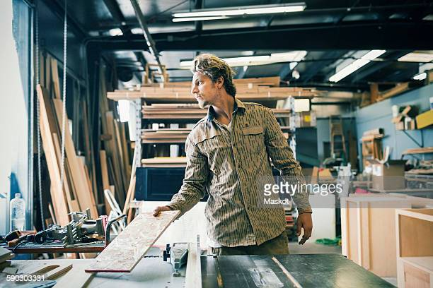 Carpenter looking away while working at table in workshop