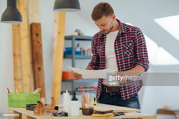 Carpinteiro Olhando um novo projecto do seu curso.