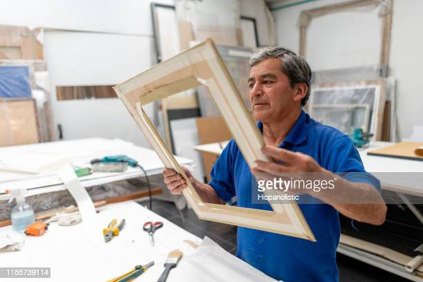 carpenter making a picture frame with wood - hispanolistic stock photos and pictures