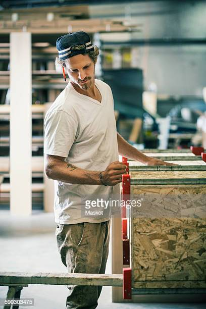 Carpenter making furniture at factory