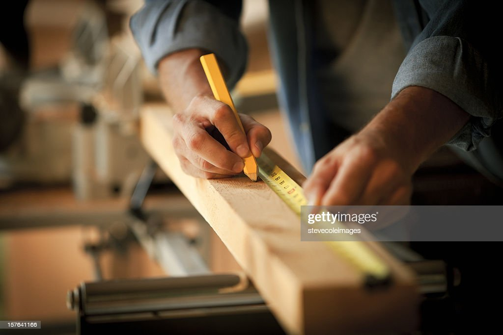 Carpenter Measuring a Wooden Plank : Stock Photo