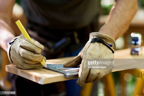 carpenter measuring a wooden plank. - work glove stock photos and pictures