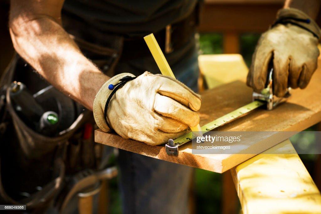 Carpenter Measuring A Wooden Plank. : Stock Photo