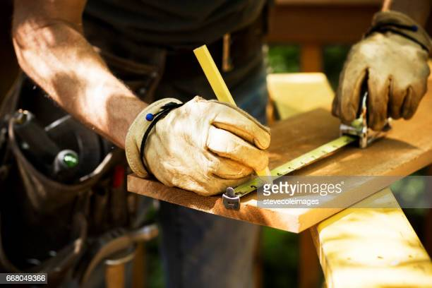 carpenter measuring a wooden plank. - building contractor stock pictures, royalty-free photos & images