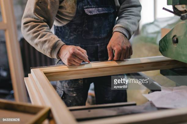 carpenter measuring a wooden plank - lumber industry stock pictures, royalty-free photos & images