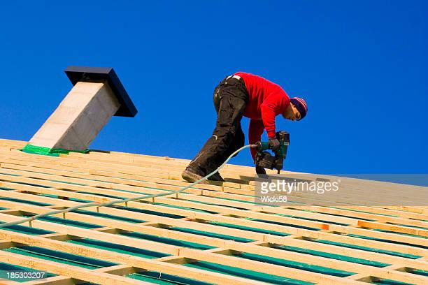 carpenter on a roof - rebuilding stock pictures, royalty-free photos & images