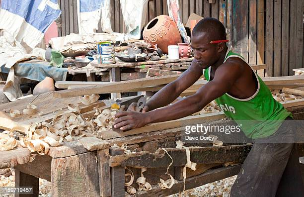 Carpenter planing a piece of timber to construct a coffin. Accra, Ghana