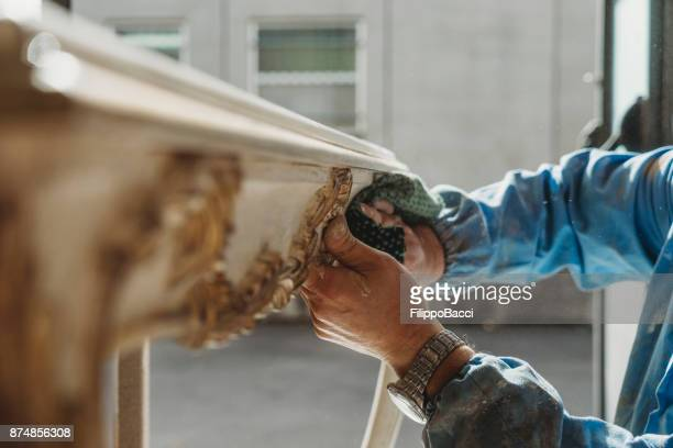 Carpenter polishing a restored table
