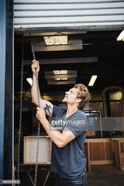 carpenter pulling shutter at entrance of workshop - shutter stock pictures, royalty-free photos & images