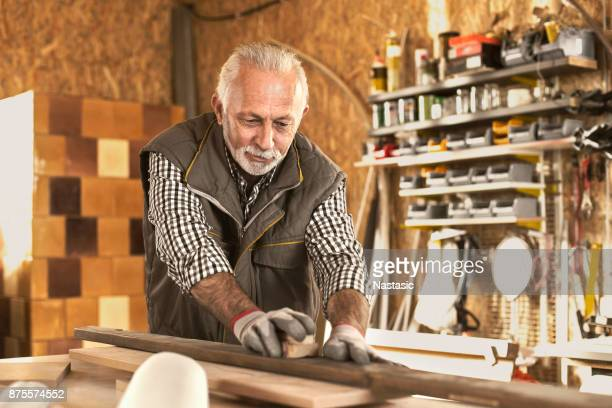 carpenter sanding wooden table with sander - bending over stock pictures, royalty-free photos & images