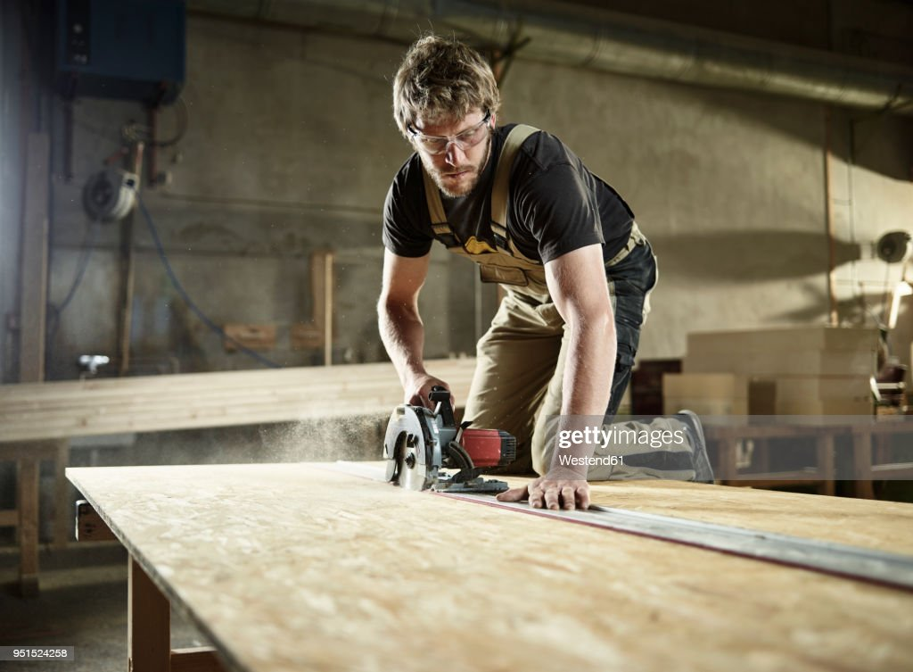 Carpenter sawing wood with handsaw : Stock Photo