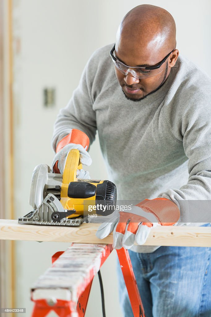 Carpenter sawing wood with power tool : Stock Photo