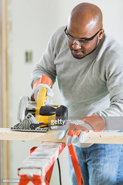 Carpenter sawing wood with power tool
