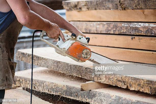 Carpenter sawing wooden plank