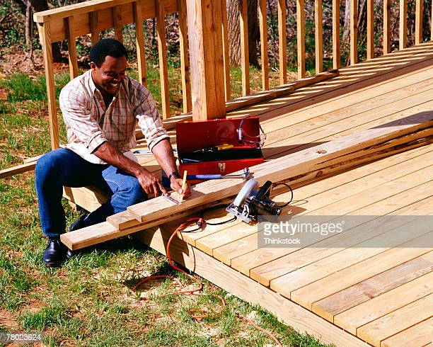 A carpenter sits on a deck measuring wood to complete a construction project.