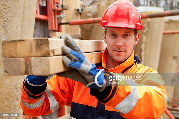 carpenter smiling at construction site. - picking up stock pictures, royalty-free photos & images