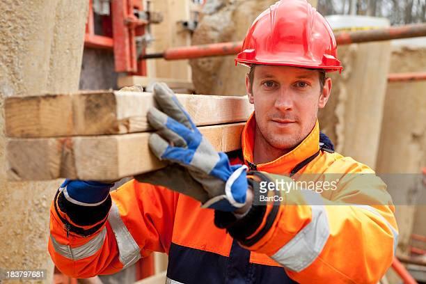 Carpenter sonriendo en solar de construcción.
