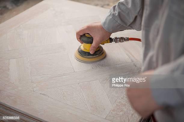 Carpenter smoothing surface of wood plank in factory, Jiangsu, China