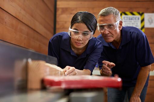 Carpenter Training Female Apprentice To Use Plane 628110788