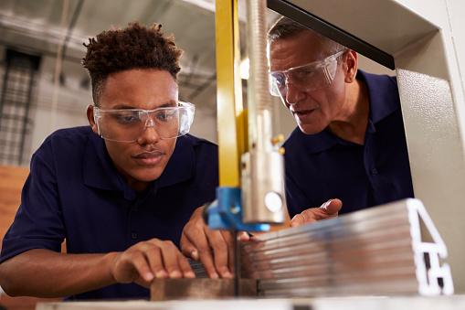 Carpenter Training Male Apprentice To Use Mechanized Saw 628110826