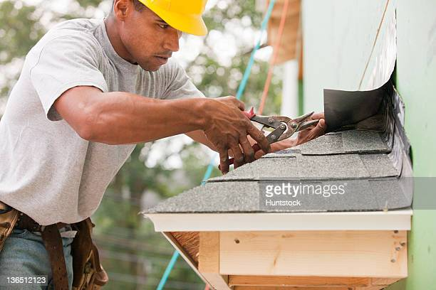 Carpenter trimming flashing on the roof