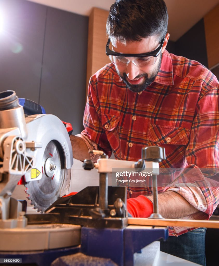 Carpenter use electric saw to cutting wooden plank : Stock Photo
