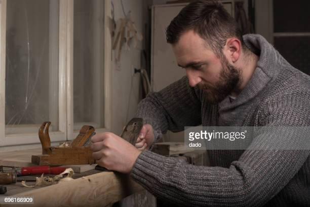 Carpenter using a hand plane